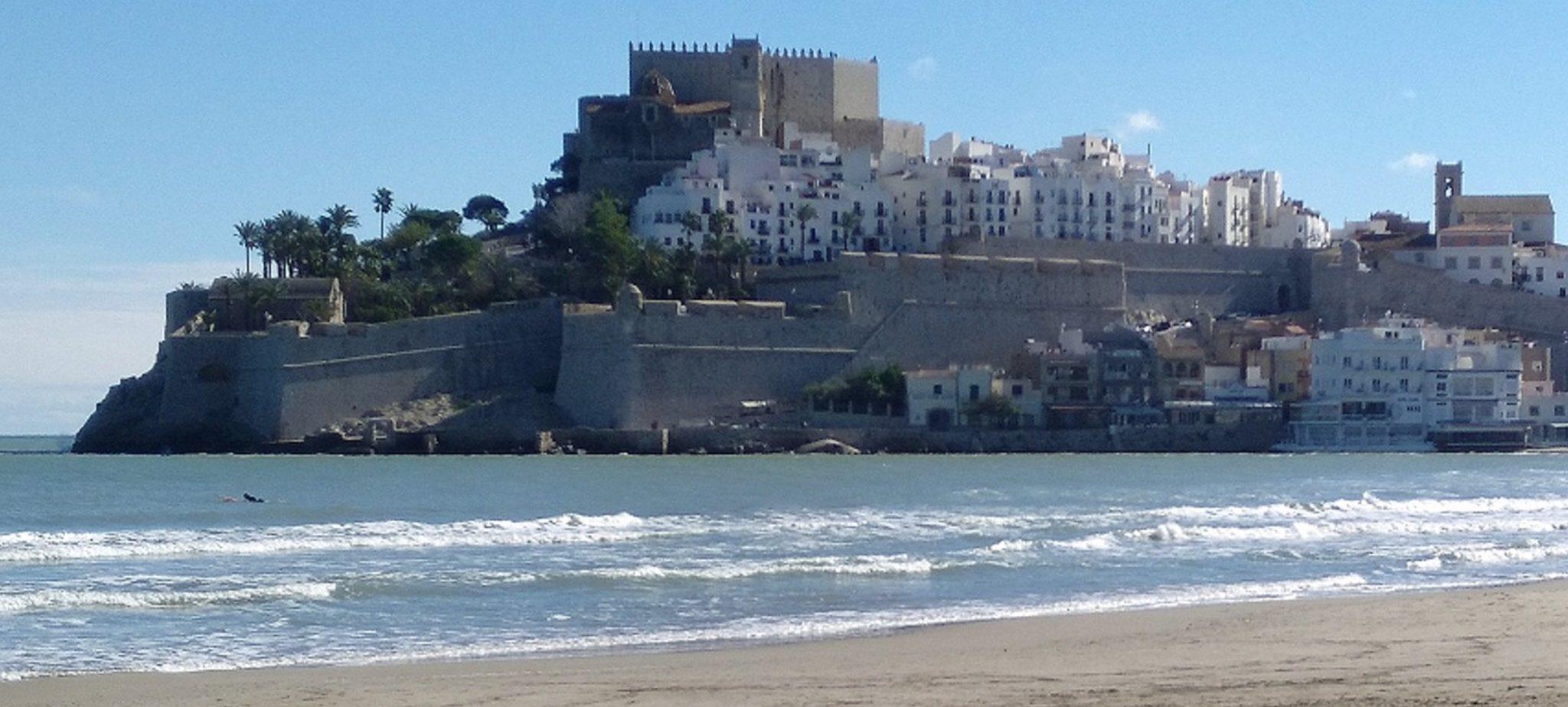 Una playa de  arena fina con su castillo medieval